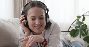 Happy woman listening music on headphones at home stock video footage