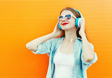 Happy young woman listens and enjoys music in headphones. Over colorful background Stock Photography