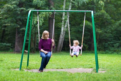 Happy young woman and a little baby girl swinging Royalty Free Stock Photo
