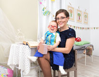 Happy young woman with little boy on her knees indoors. Happy young women with little boy in glasses on her knees indoors Royalty Free Stock Photo