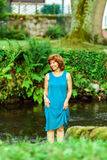 Happy young woman on the little river in a village Stock Images