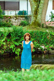 Happy young woman on the little river in a village Stock Photography