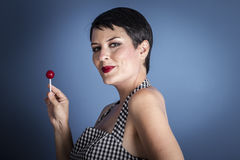 Happy young woman with lollipop  in her mouth on blue background Royalty Free Stock Photos