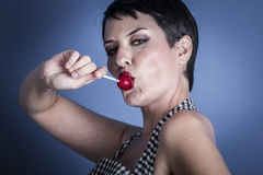 Happy young woman with lollypop  in her mouth on blue background Royalty Free Stock Photos