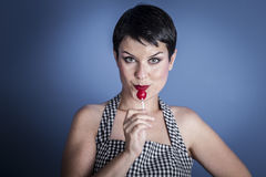Happy young woman with lollypop  in her mouth on blue background Stock Photos