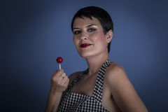 Happy young woman with lollypop  in her mouth on blue background Royalty Free Stock Image