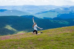 A happy young woman with long hair jumps on top of a hill Royalty Free Stock Image