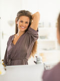 Happy young woman with long hair looking in mirror Stock Photography