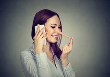 Happy young woman with long nose talking on mobile phone Royalty Free Stock Images