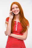 Happy young woman with long red hair talking on cellphone Stock Photos