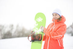 Happy young woman looking away while holding snowboard in snow Stock Image