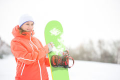 Happy young woman looking away while holding snowboard in snow Royalty Free Stock Image