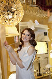 Happy young woman looking away while standing in lights store Stock Photography