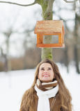 Happy young woman looking on bird feeder on tree Royalty Free Stock Photo