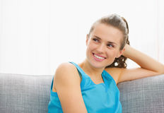 Happy young woman looking on copy space while sitting on couch Stock Images