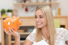 Happy young woman looking at her piggy bank Stock Photography