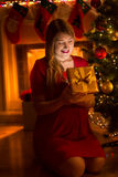 Happy young woman looking inside Christmas gift box at night Stock Photo
