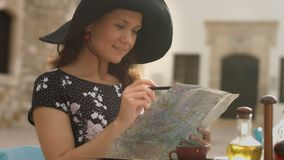 Happy young woman looking for interesting places to see, writing notes on map. Stock footage stock video