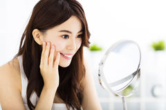 Happy young woman  looking on mirror Stock Photography