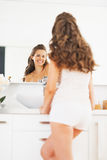Happy young woman looking in mirror in bathroom. Happy young woman with long hair looking in mirror in bathroom Stock Image