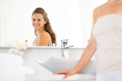 Happy young woman looking in mirror in bathroom. Happy young woman looking in mirror in modern bathroom royalty free stock photo