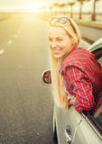 Happy young woman looking out from car window Royalty Free Stock Image