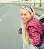 Happy young woman looking out from car window Stock Photo
