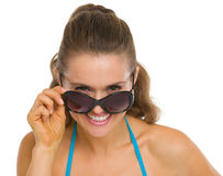 Happy young woman looking out from sunglasses Royalty Free Stock Photos