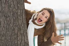 Happy young woman looking out from tree in winter park Royalty Free Stock Photo