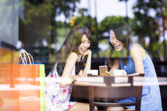 Happy young woman looking at phone in coffee shop Stock Images