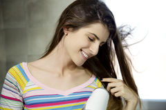 Happy young woman looking silky hair while blow drying at home Royalty Free Stock Image