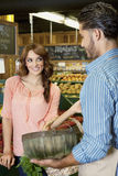 Happy young woman looking at store clerk in supermarket Royalty Free Stock Image