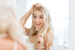 Happy young woman looking to mirror at bathroom Royalty Free Stock Photos