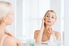 Happy young woman looking to mirror at bathroom Royalty Free Stock Image
