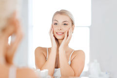 Happy young woman looking to mirror at bathroom. Beauty, hygiene, morning and people concept - smiling young woman looking to mirror at home bathroom stock photography