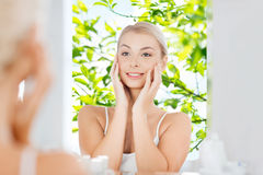 Happy young woman looking to mirror at bathroom. Beauty, hygiene, morning and people concept - smiling young woman looking to mirror at home bathroom over green royalty free stock photo
