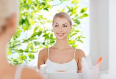 Happy young woman looking to mirror at bathroom Stock Image