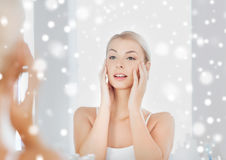 Happy young woman looking to mirror at bathroom. Beauty, hygiene, morning and people concept - smiling young woman looking to mirror at home bathroom over snow stock image