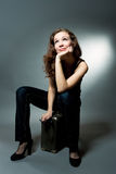 Happy young woman looking up. Sitting on suitcase isolated over gray royalty free stock photo