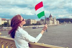 Happy young woman looking up Hungarian flag at Budapest Hungary. Happy young woman looking up onto Hungarian flag at Budapest panorama, Hungary stock photo