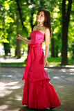 Happy young woman in a luxury long dress in summer park Stock Photos