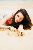 Happy young woman lying on the beach Royalty Free Stock Images