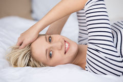 Happy Young Woman Lying On Bed Stock Photography