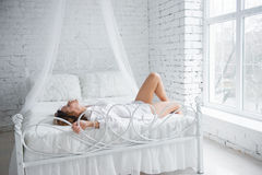 Happy young woman lying on the bed Stock Photos
