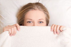 Happy young woman lying in bed under blanket Royalty Free Stock Image