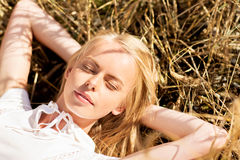 Happy young woman lying on cereal field or hay Stock Photos