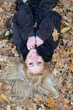 Happy young woman lying down in autumn leaves Royalty Free Stock Photos