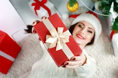 Happy young woman lying on the floor with gift box. royalty free stock photo