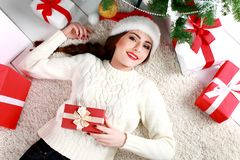 Happy young woman lying on the floor with gift box. royalty free stock images