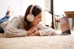 Happy young woman lying on floor with laptop and headphones. Portrait of happy young woman lying on floor with laptop and headphones Royalty Free Stock Images